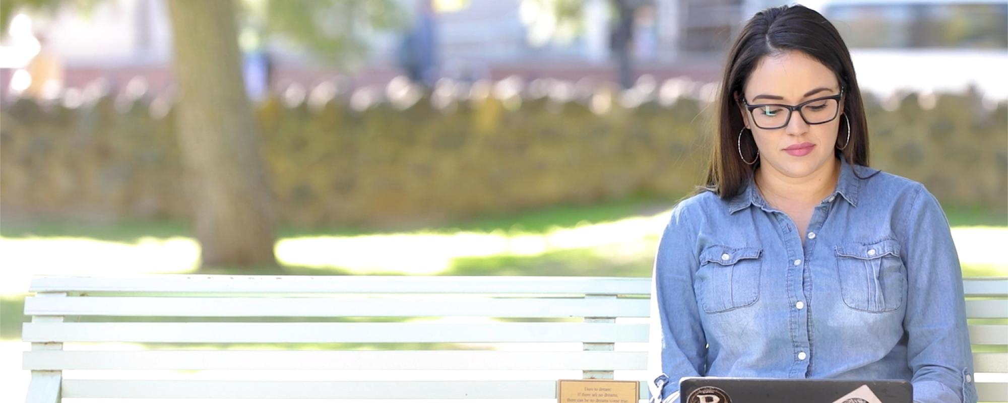 Student studying on campus park bench